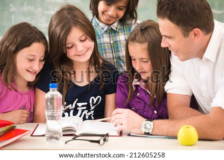 Cheerful kids learning in school with their teacher - stock photo