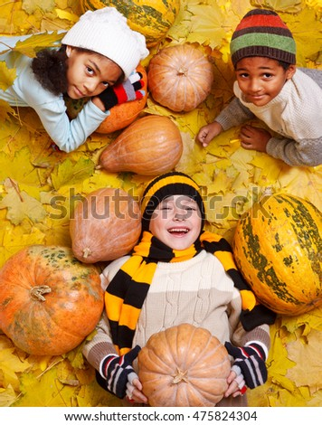 Cheerful kids of the school age lie among yellow leaves and orange pumpkins