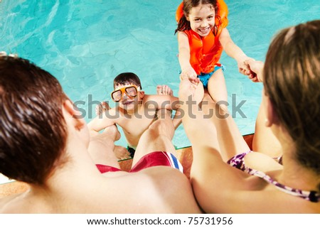 Cheerful kids playing with parents in swimming pool - stock photo