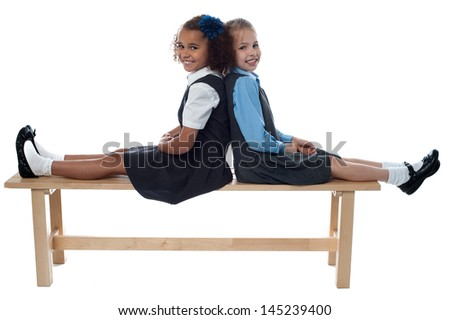 Cheerful kids relaxing on school bench - stock photo