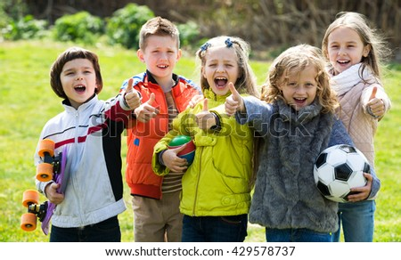 Cheerful kids with ball having fun outdoors in sunny day