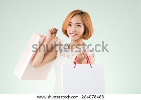 Cheerful Korean young woman posing with paper bags - stock photo
