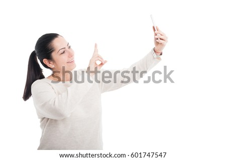 Cheerful lady taking a selfie and showing peace sign on white studio background