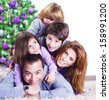 Cheerful large family having fun at home near Christmas tree, winter holidays, New Year celebration, parents with kids enjoying Christmastime - stock photo