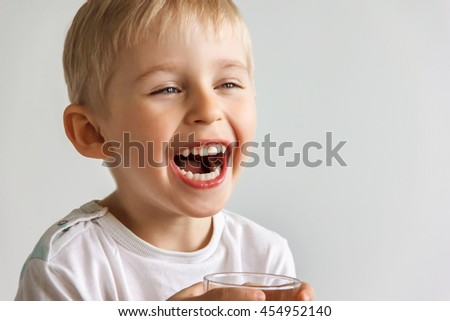 cheerful laughing boy showing healthy teeth, the child expresses emotions, dental care, very soft focus - stock photo