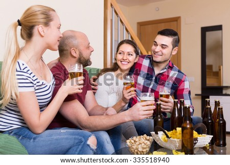 Cheerful laughing young adults drinking beer at home. Selective focus - stock photo