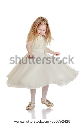 Cheerful little blonde girl with flowing long hair in white ball long dress and white stockings . The girl whirls around-Isolated on white background - stock photo