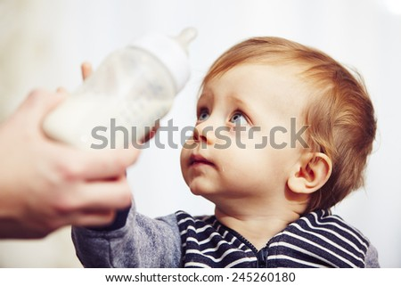 Cheerful little boy after feeding - selective focus - stock photo