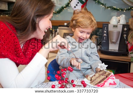 Cheerful little boy and his mother laughing and eating Christmas cake. They are enjoying on winter holidays at home. - stock photo
