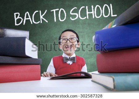 Cheerful little boy back to school and smiling in the class while wearing uniform and studying - stock photo