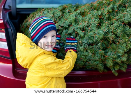 cheerful little boy holding christmas tree - stock photo