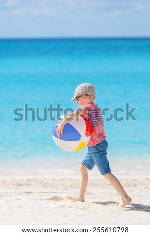 cheerful little boy holding colorful beach ball and having fun at tropical vacation - stock photo