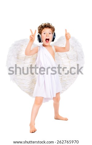 Cheerful little boy in a costume of angel listening to music in headphones and singing. Cupid. Valentine's day. - stock photo