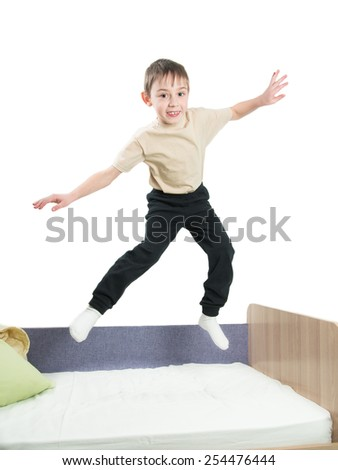 Cheerful little boy in a shirt and trousers jumping on the bed and waves his hands on a white background - stock photo