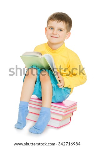 Cheerful little boy in a yellow shirt and blue shorts sits on books and reads textbook - Isolated on white background - stock photo