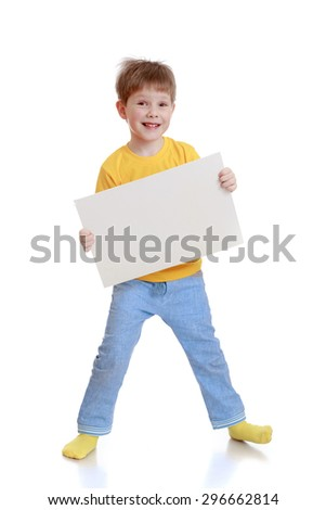 Cheerful little boy in a yellow t-shirt and jeans holding in front of a rectangular sheet of cardboard on which you can write ads - isolated on white background - stock photo