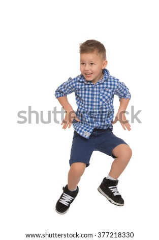 Cheerful little boy in blue plaid shirt and shorts jumps - Isolated on white background