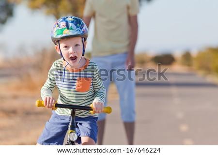 cheerful little boy in helmet at balance bike - stock photo