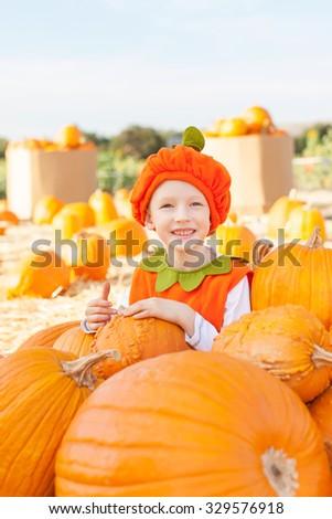 cheerful little boy in pumpkin costume enjoying halloween time at pumpkin patch - stock photo