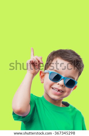 Cheerful little boy in sunglasses showing thumbs up gesture, on green background - stock photo