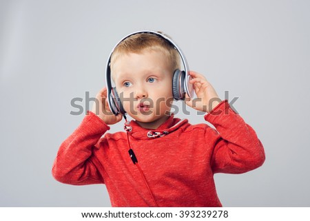 Cheerful little boy listening to music in headphones and singing a song. Studio shot of boy with headphones - stock photo