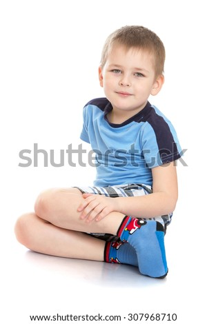 Cheerful little boy meadow t-shirt and shorts is sitting on the floor cross-legged-Isolated on white background - stock photo