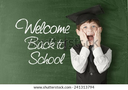 Cheerful little boy on blackboard. Looking at camera. School concept - stock photo