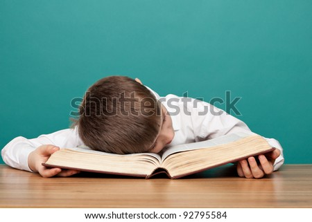 cheerful  little boy sitting at the table  and sleeps on the book. School concept - stock photo