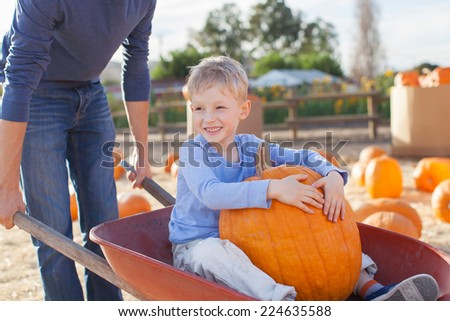 cheerful little boy sitting in the cart with huge pumpkin, having fun with his father at pumpkin patch - stock photo