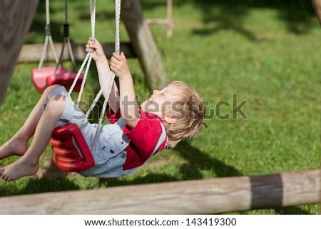 Cheerful little boy swinging in playground - stock photo