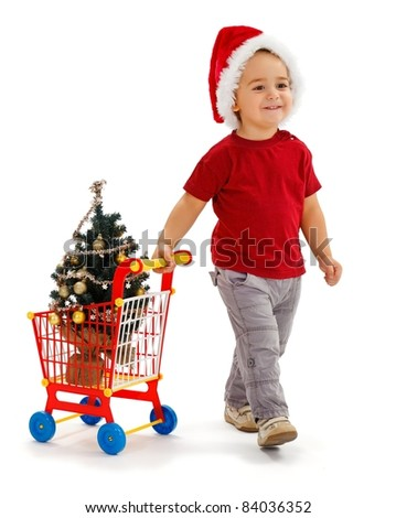 Cheerful little boy wearing Santa hat, pulling toy shopping cart, he just purchased a small, decorated Christmas tree - stock photo