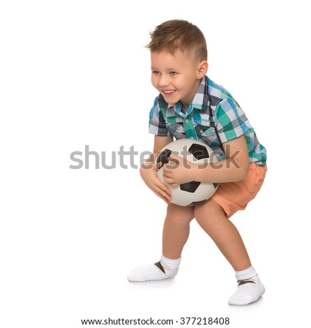 Cheerful little boy with a fashionable hairstyle catches a soccer ball - Isolated on white background