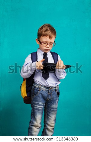 Cheerful little boy with big backpack holding digital tablet against blue background. Child playing games on a touch pad. School concept. Back to School