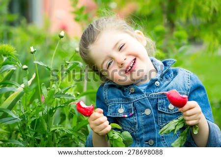 Cheerful little child eating fresh radishes in the garden - stock photo