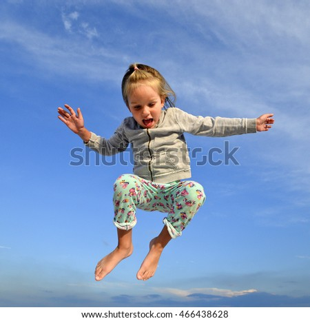 Cheerful little child girl jumping and hovering in the air on the background of blue sky. Child playing and having fun/Girl playing, jumping, hovering/Little girl playing, jumping, hovering in the air