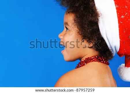 Cheerful little child in Christmas hat against blue background - stock photo