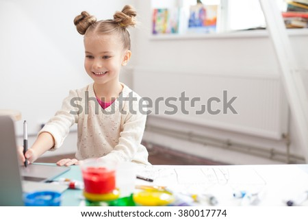 Cheerful little child is creating beautiful image - stock photo