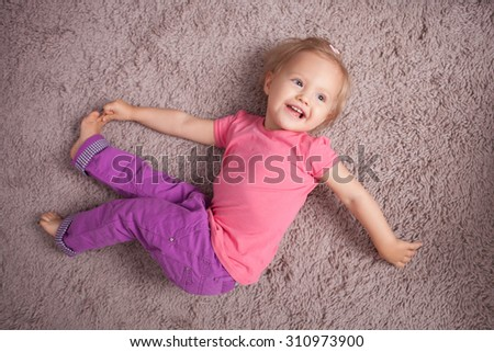 Cheerful little child is lying on carpet with pleasure. She is resting and smiling. The girl is stretching her body and touching her leg with her hand. She is looking aside with interest - stock photo