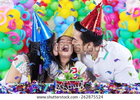 Cheerful little girl celebrate her birthday party with her parents and get kiss - stock photo