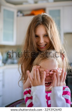 Cheerful little girl closes eyes to her sister. - stock photo