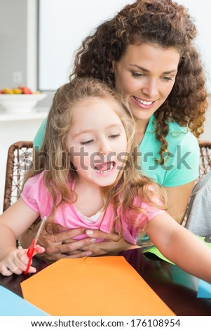 Cheerful little girl doing arts and crafts with mother at the table at home in kitchen - stock photo