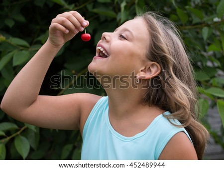Cheerful little girl eating a cherry - stock photo