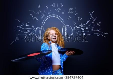 Cheerful little girl enjoys the music in headphones. Studio shot. - stock photo