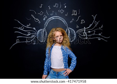 Cheerful little girl enjoys the music in headphones. Studio shot. - stock photo