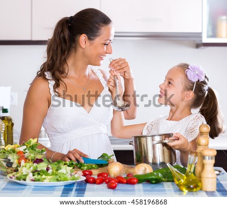 Cheerful little girl helping mother to prepare stewed vegetables in kitchen - stock photo