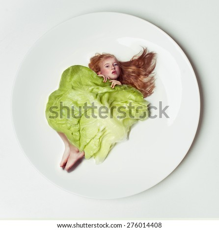 Cheerful  little girl holding a head of cabbage/beautiful little with green cabbage (savoy) isolated over white background - stock photo