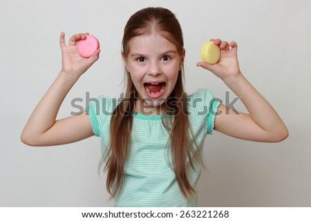 Cheerful little girl holding macaroons - stock photo