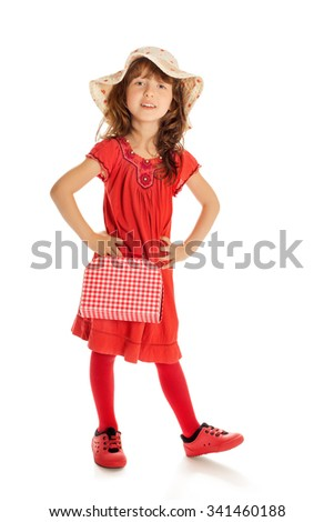 Cheerful little girl in a red dress and hat holding a briefcase-Isolated on white background - stock photo