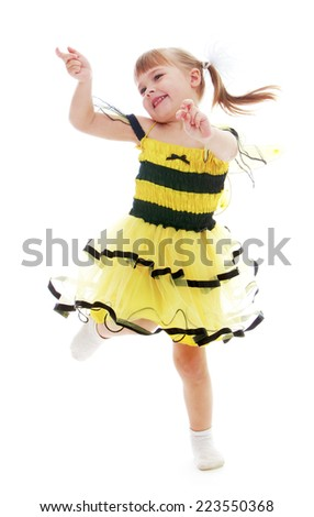 Cheerful little girl in a yellow dress jumping and having fun. Happy childhood, fashion, autumnal mood concept. Isolated on white background - stock photo
