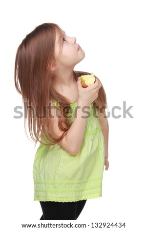 Cheerful little girl in bright clothes eating an apple on white background on Food and Drink